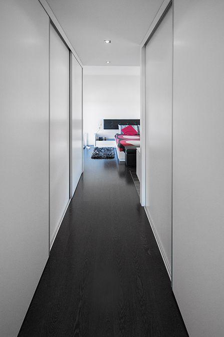 Pasillo vestidor en dormitorio de casa minimalista | Chiralt Arquitectos Valencia. #armario #blanco #dormitorio #parquet #oscuro