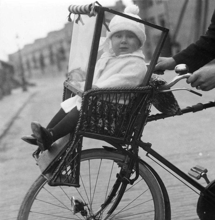 Vervoer, fietsonderdelen: kinderzitje stoeltje met kind/peuter voorop de fiets, Amsterdam, Nederland 1925.