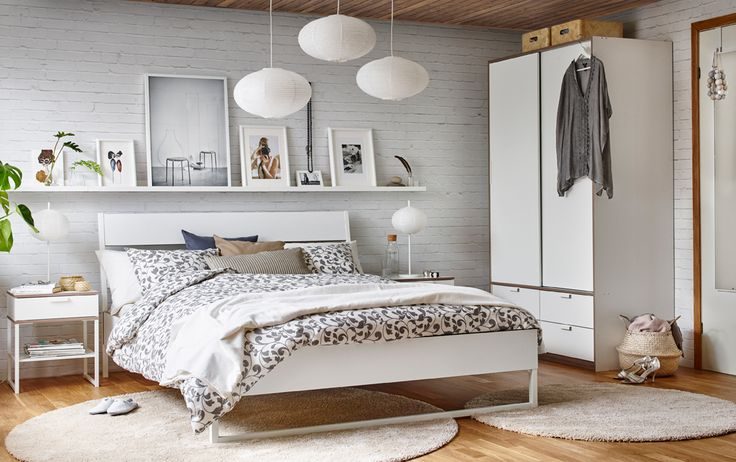 Double bed in white/light grey in a bedroom with white brick walls and wood floor.