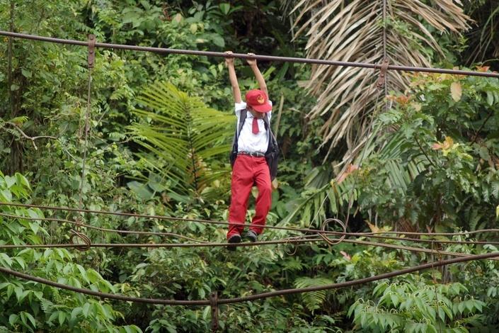 Мальчик идет в школу, Пинту Габанг, Индонезия. Из-за сильных дождей подвесной мост, который был единственным путем из его деревни до учебного заведения, рухнул, и люди вынуждены преодолевать реку по канатам на высоте 10 метров