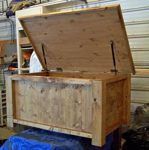 Large solid wood rustic toy box or hope chest with gas struts for stays.