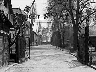 """Auschwitz I  Main Camp Entrance Gate   As one enters the camp you pass under the infamous words """"Arbeit Macht Frei"""" (Work Makes Freedom). Then, just beyond the gate and to the right, is where the band played to emaciated inmates as they left and returned from work."""