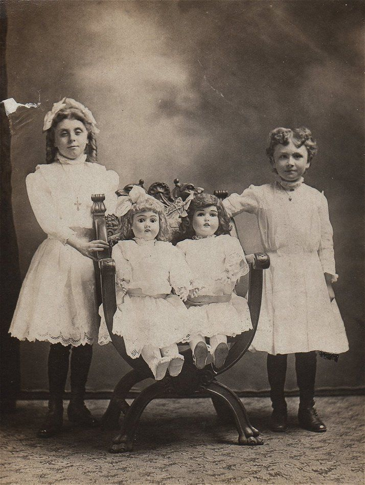 Antique photo of little girls with their dolls, circa 1880 - 1900.