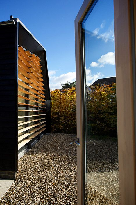 This house features blackened timber cladding and glazed walls shielded by wooden louvres. Our BIMA louvres like this move according to the sun and bear a hidden message - coatesdesign.com