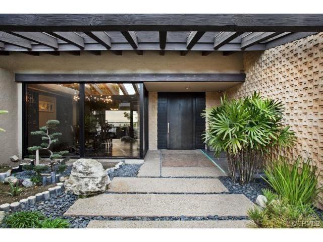 walkway to front door with plantings, stones and bolder.