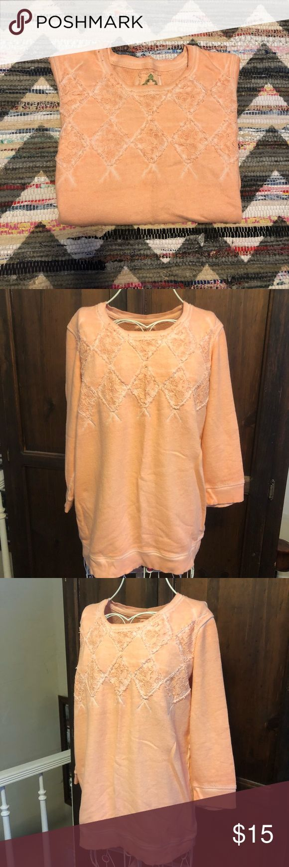 """Ruff Hewn Washed coral peach lace sweatshirt What a comfy cute lounge piece! Ruff Hewn Brand, size Medium, a made to look worn intentional distressing and fading around the seams. Washed light coral or peach color. Cute lace diamond cut outs on the chest, and super soft terry towel lining on the inside. About 21"""" across the chest laying flat, and about 26"""" long from shoulder to hem. A couple minor flaws to note: two very small dark dots by the neckline, and a small stain less than dime size…"""