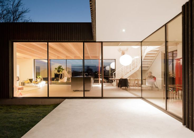 A modern patio looks into the double-height living space.