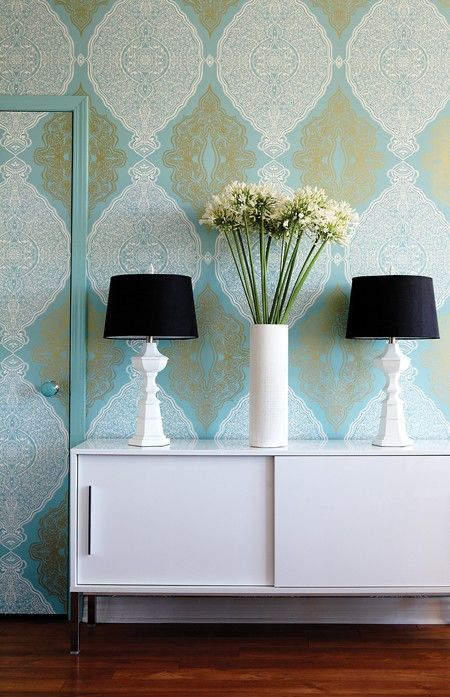 Wallpaper continued across the door and painted frame same color, great idea.