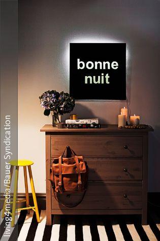 """""""Bonne nuit"""" wünscht die selbstgemachte schwarze Wandleuchte über der klassischen Holzkommode. Die kreative DIY-Idee besteht aus einer schwarzen Platte mit ausgeschnittenen Buchstaben. Das Leuchtmaterial wird dahinter befestigt und sorgt für eine gemütliche indirekte Beleuchtung, die den Raum in ein gemütliches Licht taucht."""