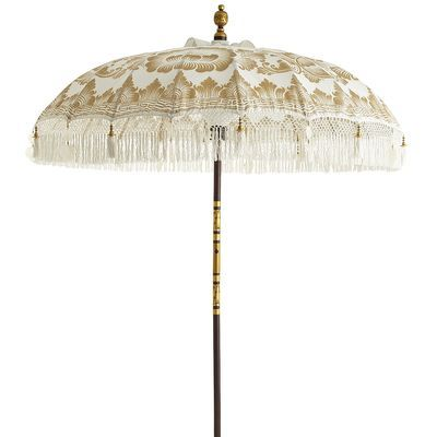 """This spectacular fringed, tasseled and ornamented umbrella is known as """"tedung"""" in Balinese dialect, which means """"to guard."""" Entirely handcrafted in Bali—from the carved pole to the intricately hand-gilded canopy—each umbrella is one of a kind and takes 10 days to create. Often used  in its native land for festive ceremonies and parades in colors to reflect the occasion. In this case, white represents purity, peace and knowledge."""