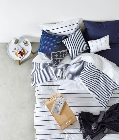 Crisp and clean, this navy and white bedding will sharpen up even the softest bed. Photo by Aya Brackett.