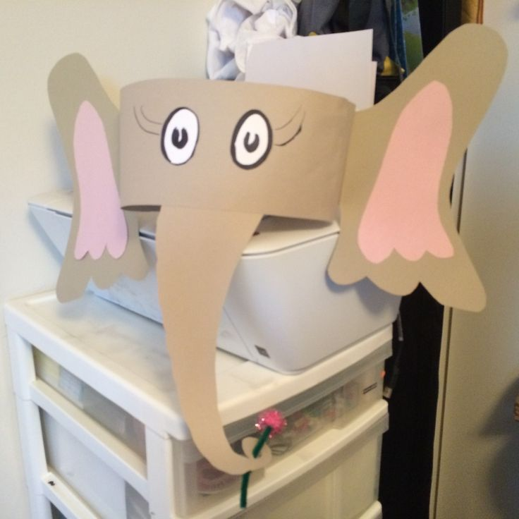 "Horton Hears a Who Hat – Cut 2 4.5""x18"" grey strips.  Draw Horton type eyes on white paper & cut out, glue to the center of 1 of the grey strips.  Cut 2 elephant ear shapes out of grey paper, at the inner part of the ear draw a flap that is connected to the ear before you cut out it will help you attach it.  Cut 2 pink inner ears & glue to center of ears. Cut elephant trunk out – at the end of the trunk cut it so it curls around & has a hole in the center–flower goes here.  Continued on 2nd…"