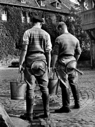 Two young men attending agricultural school wearing milking stools, ready for lessons in Prussia.....from the historical archives of LIFE Magazine. Related Categories: Alfred Eisenstaedt, People (LIFE)