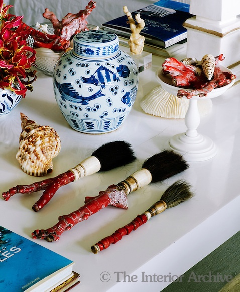 One of a pair of white coffee tables in the living room displays a collection of objects, shells and coral