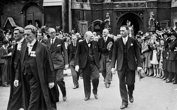 Prime Minister Winston Churchill waving to a waiting crowd as he leaves the Houses of Parliament after the news of the defeat of Nazi Germany
