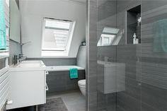 Moderne kleine badkamer met ligbad, dubbele wastafel, toilet en douche.