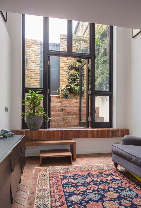 Old upholsterer's workshop in London transformed into a narrow brick home.