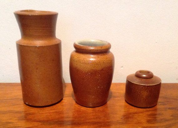 A collection of three mid brown stoneware pots from the early 1900s.  1. Tall narrow pot..5 tall, 2.2 across top. This one has a slightly wavy neckline, small chip at base and glaze faded to one side.  2. Urn shaped pot...4 tall, 1.7 across top, chip to top.  3. Inkwell..1.6 tall,1.5 diameter, fading to glaze...clay protrusion at rear.  These would make a nice addition to any collection. We have lots more stoneware in many colours and sizes...please see our other listings.  Please note: We…