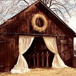 Barn with curtains and huge wreath.