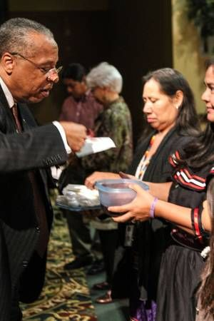 The Rev. Robert Hayes Jr., bishop of the Oklahoma United Methodist Conference and Oklahoma Indian Missionary Conference, receives Communion from Tamara Wilson, a member of the Yuchi tribe. The bishops were urged to use the knowledge they gleaned at a service of repentance to promote healing and reconciliation between the global United Methodist Church and indigenous peoples around the world.