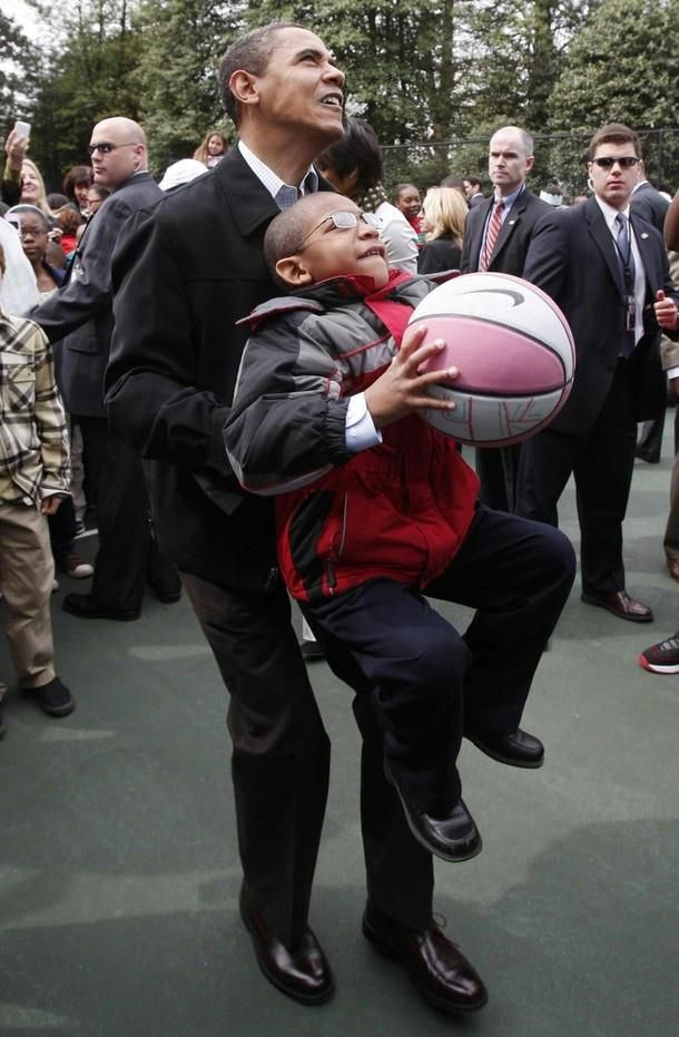 President Barack Obama picks up a boy to help him shoot a basketball as part of the Annual Easter Egg Roll on the South Lawn at the White House in Washington, April 13, 2009.