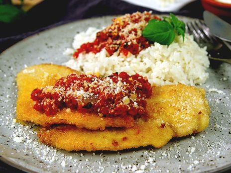 Kyckling panerad i parmesanost serveras med en fyllig tomatsås och kokt ris. Mums!