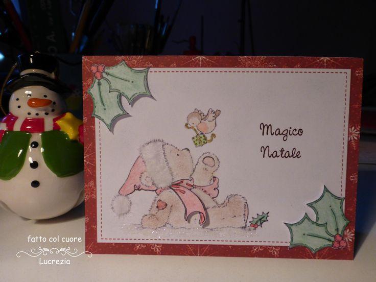 Biglietto per le feste natalizie: fra la neve e l'agrifoglio un dolcissimo pettirosso porta un dono all'amico orsetto