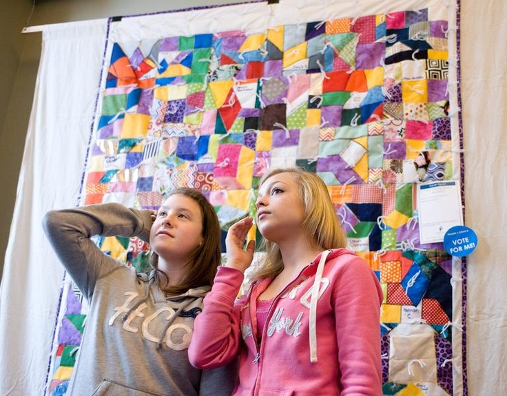 Standing in front of one of three quilts their seventh-grade class made, Hallie Luck, right, and Aly Day, search for more clues as they join classmates from Monticello Middle School at Cunningham Children's Home in Urbana on Thursday, April 11, 2013.  (Purchase a Print |