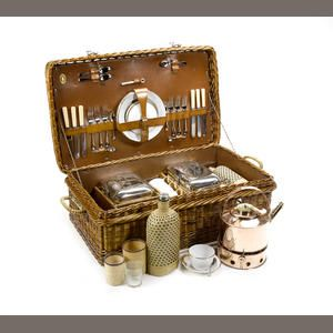 A fine wicker-cased six-person picnic set, by G W Scott & Sons, c1909 dark wicker case with wicker handles opening to reveal brown leathercloth interior fitted with copper kettle and stand, two large wicker-covered drinks bottles, three enamel-based food boxes, six stacking glasses in wicker containers, a set of six wicker-handled enamel teacups, and ceramic butter jar, with gilt-edged enamel plates and saucers and full compliment of cutlery and bottle opener Sold for £5,750 inc. premium