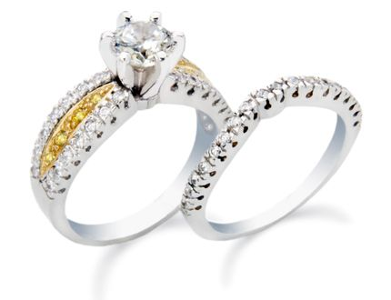 White and yellow gold engagement ring featuring a round center diamond with white and yellow diamond melee.