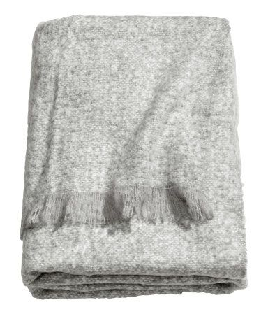 Light gray. Throw in soft woven fabric with fringe on short sides.