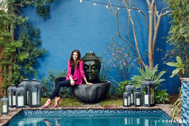 Nina Dobrev's bright outdoor space with a pool and a giant Buddha fountain