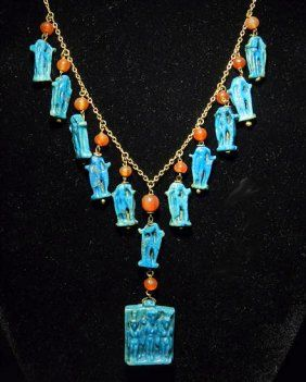 "An Important Egyptian Faience Amulet Gold Necklace ~ Stunning and wearable! Comprised of 12 ancient Egyptian amulets including 11 matched Amarna Period (18th Dynasty, ca 1549 to 1292 BC) amulets of Isis, each with an ancient carnelian bead, and large central pendant of the ""holy triad"" including Nephys, Isis and Horus; all amulets set into 18 karat gold in the 1950s."