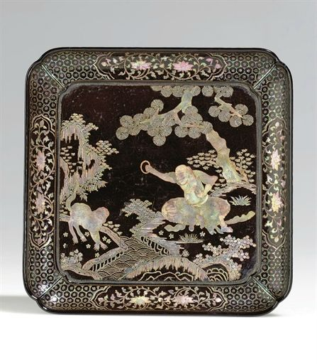 A rare mother-of-pearl-inlaid black lacquer dish, Ming dynasty, 16th century.  The dish of quatrefoil form elaborately inlaid in the recessed center panel with mother-of-pearl with a luohan seated beneath a pine tree upon a large rock and dressed in open robes tied at the waist, his right hand raised holding a ring which he uses to beckon a tiger gazing back at him from across a narrow stream, framed by four shaped cartouches containing lotus scroll reserved on a diaper ground