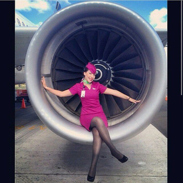 Volaris Airlines Stewardess sitting on the engine cowling.