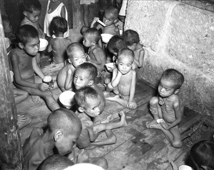 Japanese orphans whose parents were killed, or who were abandoned during the Battle of Okinawa (codename: Operation Iceberg), are photographed eating their meager rations in Koza Orphanage. Approximately 100,000 to 150,000 Okinawan men, woman, and children lost their lives during the nearly three months of fighting. Koza Orphanage housed around 3,000 to 4,000 children directly after hostilities ended. Sumiyoshi, Okinawa, Okinawa Prefecture, Japan. June 1945.