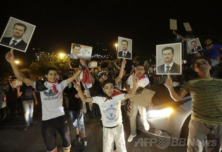シリアの首都ダマスカス(Damascus)の路上で、バッシャール・アサド(Bashar al-Assad)大統領再選を祝う人々(2014年6月4日撮影)。(c)AFP/JOSEPH EID ▼5Jun2014AFP|シリア大統領選、アサド氏が再選 反体制派「茶番」と非難 http://www.afpbb.com/articles/-/3016819 #Damascus