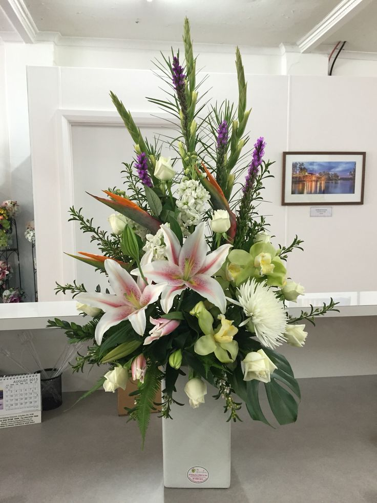Large flower arrangement of gladiolus, liatris, cymbidium orchids, lilies, disbud chrysanthemum and stock.