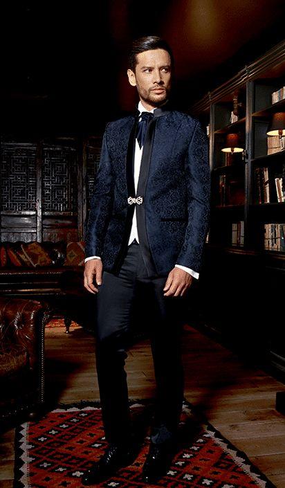 Ce costume bleu marine confectionné dans un scintillant tissus à motif adopte un col mao noir satiné qui rappellera la couleur du pantalon.Il est accompagné d'un gilet blanc et se mariera parfaitement avec une lavallière marine ou blanc.