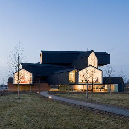 """La VitraHaus progettata  dallo studio Herzog & De Meuron è stata concepita come spazio espositivo per i  mobili appartenenti alla """"Home Collection"""" di Vitra. La costruzione a cinque piani è realizzata con """"corpi"""" ammucchiati, quasi senza criterio. Le facciate di ogni corpo sono interamente realizzate in vetro. Le abitazioni si sporgono come fossero tante travi per cinque metri dando l'impressione di case impilate senza criterio l'una sopra l'altra."""