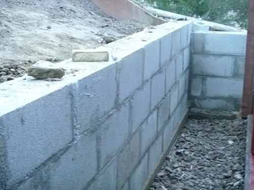 Finished lower cinder block retaining wall french drain Cinder block retaining wall