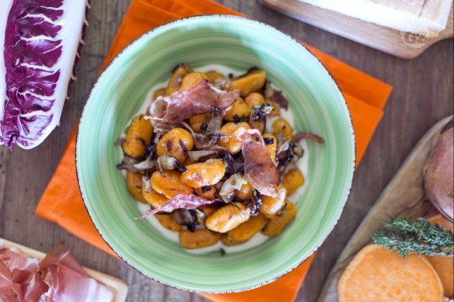 Gli gnocchi di patate dolci al radicchio e speck sono un primo piatto dal gusto deciso e stuzzicante realizzato con le tipiche patate americane.