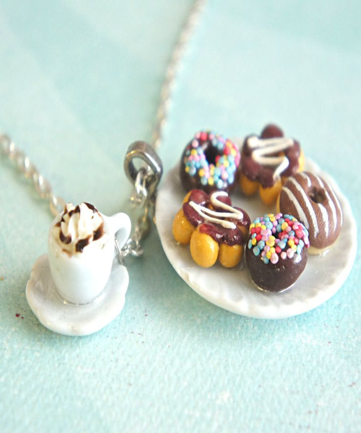 This necklace features a plate of handmade donuts sculpted from polymer clay along with a coffee cup charm. The ceramic plate pendant measures 1.5 inches in diameter. Both charms are attached to a sil