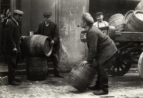 Arbeiders bij bierwagen en biervaten van Heineken Bier Brouwerij, Amsterdam, Nederland, augustus 1913. Deze foto is gebruikt voor een in scène gezette reeks van drie foto's (waarvan de overige twee opnamen niet bewaard zijn) die het fenomeen van 'Haftenbrouwen' illustreren in tijdschrift Het Leven bij een artikel op het verbod op 'Haftenbrouwen' in de nieuwe politieverordening van Amsterdam. Haftenbrouwers zijn mensen die hun kostje bij elkaar scharrelen door 's ochtends de bierwagens in de…