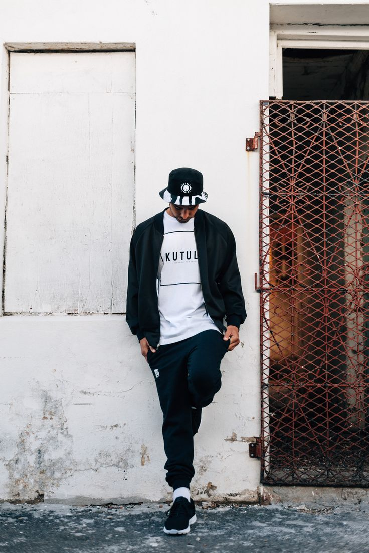 Daniel Band wears the Black Reversible Urban Camo Bucket Hat with Lion Emblem, the Reversible Unisex Urban Camo Bomber Jacket, the White Kutula Box T-Shirt and the Black Kutula Tracksuit Bottoms with the Lion Emblem >> KUTULA