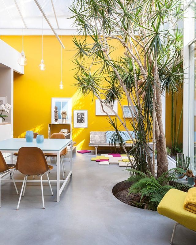 Furnished with vintage Eames chairs, a second-hand sofa, and pendants and tables designed by Nathalie, the space is kept purposefully casual. She painstakingly mixed and tested the paint for the mustard-yellow walls herself—15 times—to match the hue of a Kvadrat textile. Architecture by Nathalie Wolberg and Tim Stokes. Photo by Tim Van de Velde.