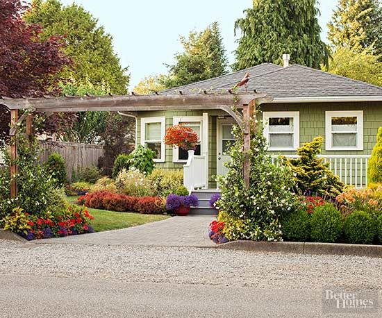 Measuring a generous 14 feet wide by 8 feet tall, the Craftsman-style arbor lends stature to this Seattle front yard, where mixed evergreen plants and boxwood shrubs further enclose the entry.