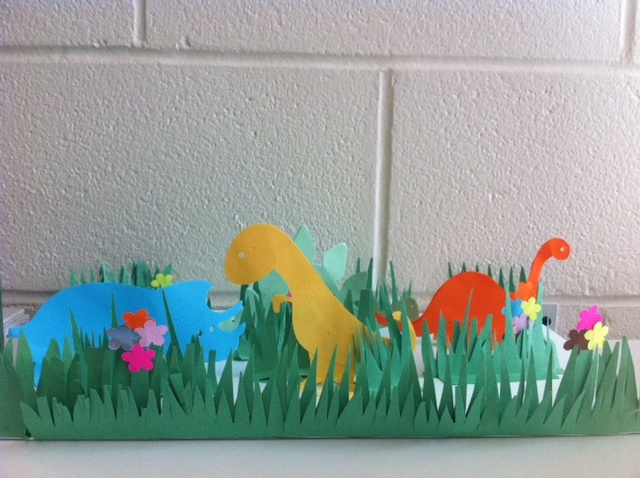 """Summer Reading craft sample for """"Dig into Reading"""". A Jurassic Park using Ellison die cut outs and green paper as grass."""