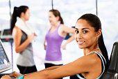 Schöne junge Frau, die Fitness-Ausrüstung lächelt selbstbewusst