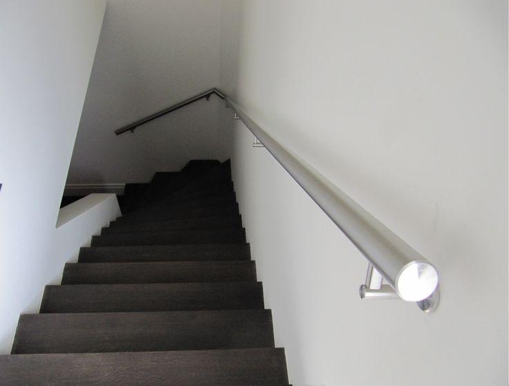 Strakke RVS trapleuning en een hardhouten donkere trap.